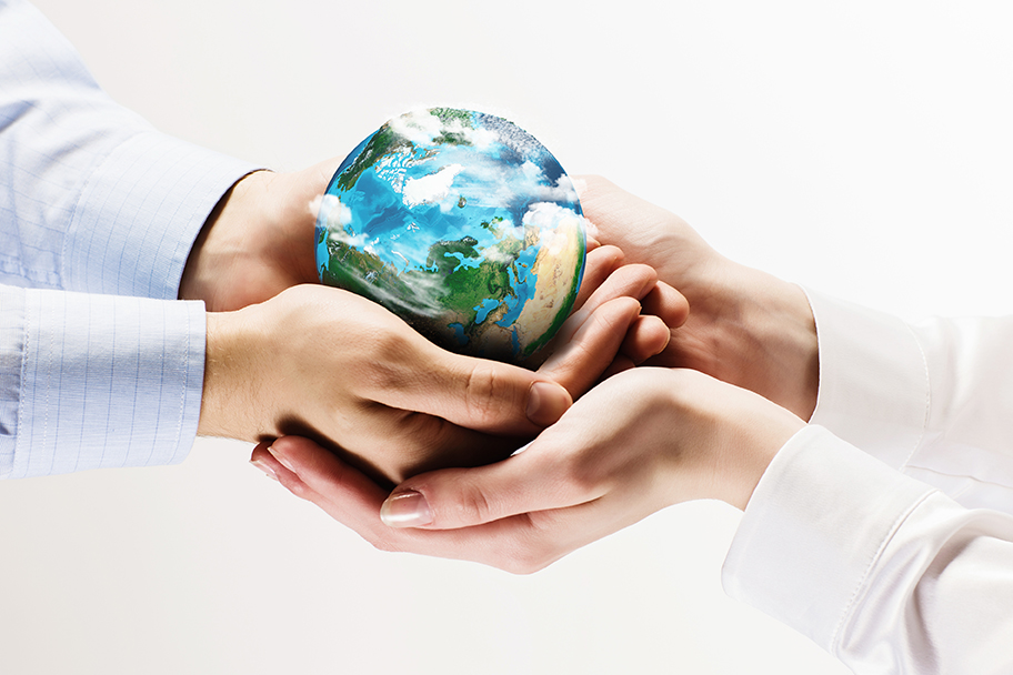 Two people holding hands and holding the globe